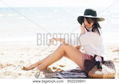 Stylish Hipster Girl In Hat Sitting On Beach And Tanning Near Sea Waves. Summer Vacation. Happy Boho