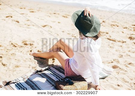 Stylish Hipster Girl In Hat Sitting On Beach With Straw Bag And Tanning. Summer Vacation. Happy Youn