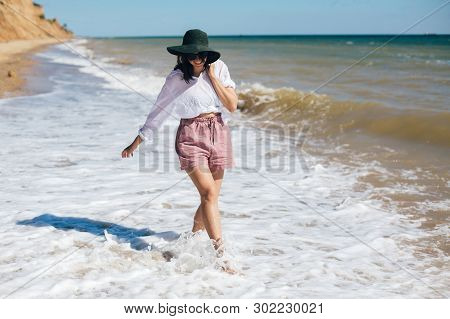 Happy Young Boho Woman Walking In Sea Waves In Sunny Warm Day At Tropical Island And Blue Sky. Space