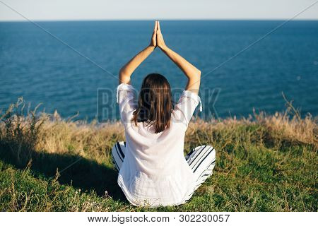 Stylish Hipster Girl Sitting And Doing Yoga On Mountain Peak With View On Sea And Sky. Happy Woman P