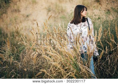 Stylish Hipster Girl Posing At Wildflowers, Long Herbs On Beach And Cliff Near Sea. Summer Vacation.