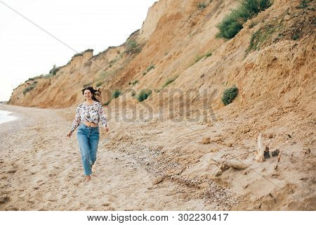 Stylish Hipster Girl Running On Beach At Sea And Smiling. Happy Fashionable Boho Woman Relaxing At S
