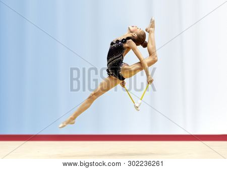 Delightful acrobatic jump with a splits performed by a young gymnast, a girl gymnast dressed in rhinestone embroidered leotard participates in the championship of rhythmic gymnastics poster