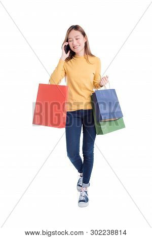 Full Length Of Beautiful Asian Woman Holding Many Shopping Bags And Mobile Phone Isolated Over White