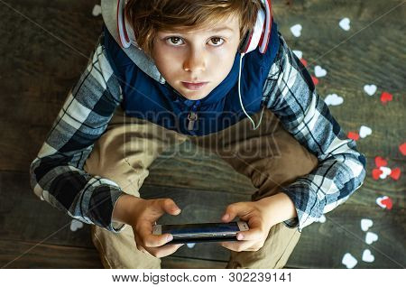 Fashionable Teenager Boy In Headphones And With A Mobile Phone Playing An Internet Game. The Depende