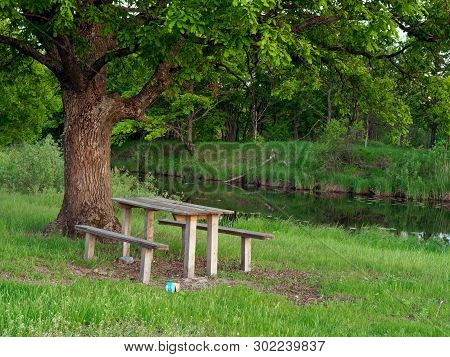 Sitting Area With A Table And A Bench By The River In The Evening On A Green Background
