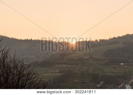 Sunset With Colorful Sky Above Forest In Rural Landscape Witth Fields, Forest And Small Hills Above