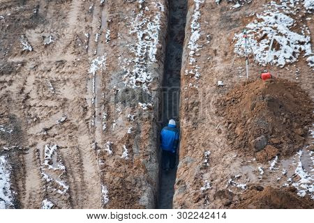 Construction Worker Walks In Trench At The Site. Top View