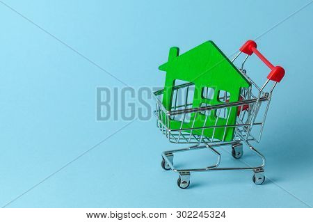 Shopping Cart And House On A Blue Background. Buying And Selling Real Estate. Copy Space For Text