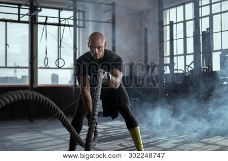 Bald athlete doing battle rope exercise at fit gym. Concentrated african man doing  fit exercise while working out in gym. Focused man in sportswear training exercise.