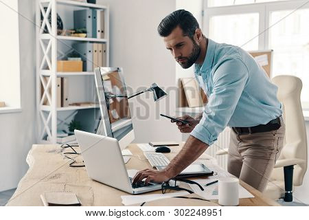 Inspired To Work Hard. Young Modern Businessman Using Smart Phone And Computer While Working In The