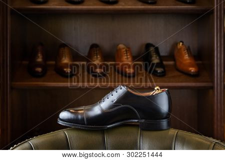 Black full grain leather shoe in front of wooden display in men shoes boutique store.