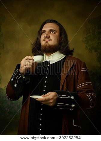 Young Man As A Medieval Knight On Dark Studio Background. Portrait In Low Key Of Male Model In Retro