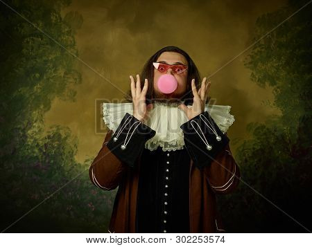 Young Man As A Medieval Knight In Sunglasses On Dark Studio Background. Portrait In Low Key Of Male