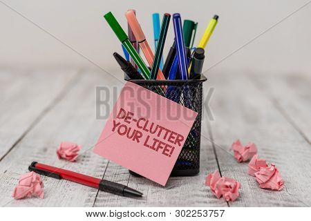 Conceptual hand writing showing De Clutter Your Life. Business photo text remove unnecessary items from untidy or overcrowded places Writing equipment and paper scrap with blank sheets on wooden desk. poster