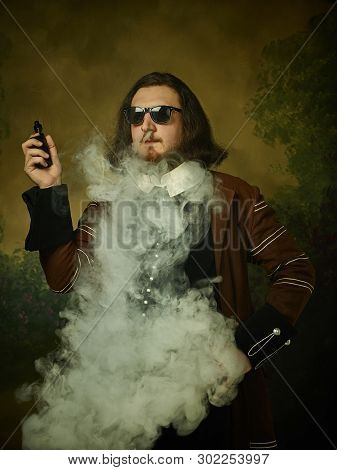 Young Man As A Medieval Knight In Sunglasses On Dark Studio Background. Portrait Of Male Model In Re