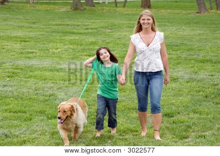 Mother And Daughter Walking The Dog