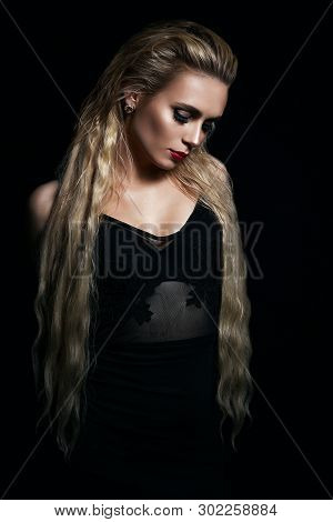 Beautiful Blonde Model Girl With Long Curly Hair . Hairstyle Wavy Curls . Red Lips And Nails Manicur