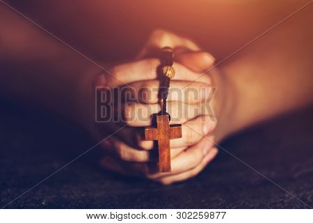 Woman holding a rosary and praying. Christian religious symbols. Faith and spirituality.