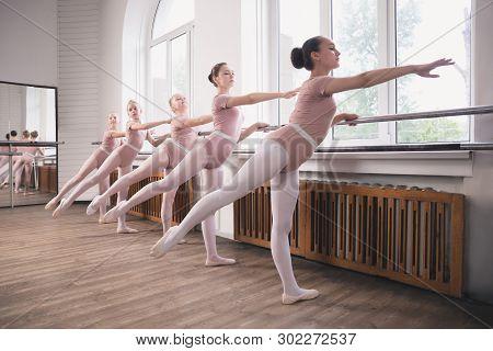 Young Graceful Female Ballet Dancers Dancing At Training Studio. Beauty Of Classic Ballet. Girls Per
