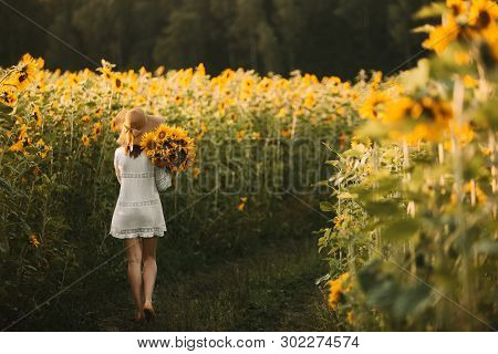 Young Woman In White Dress And Hat Holding A Bouquet Of Sunflowers And Goes On The Road To The Sunse