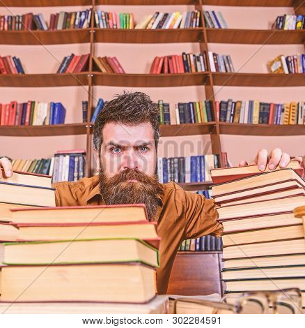 Teacher Or Student With Beard Sits At Table With Glasses, Defocused. Man On Strict Face Between Pile