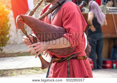 A Man Plays A Musical Bagpipe, A Close View