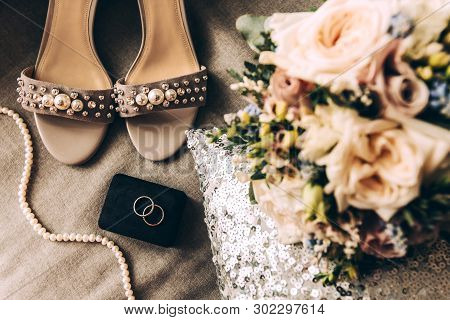 Wedding Accessories On A Pillow With Sequins: Two Silver Wedding Rings, Bridal Bouquet, Shoes And Be