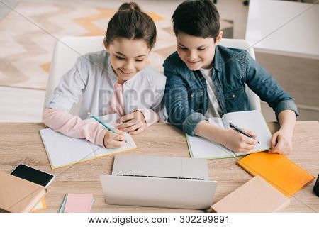 Smiling Brother And Sister Writing In Notebooks And Using Laptop Together