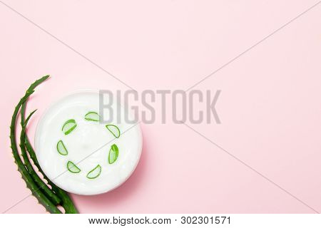 Jar Of Cream And Slice Of Aloe Vera On A Pink Background. Top View
