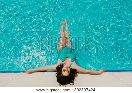 Attractive Busty Curvy Woman In Yellow Sunglasses And A Blue Swimsuit Resting By The Pool. Stylish A