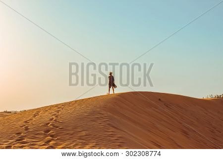 Young Beautiful Girl In A Long Dress And A Hat In The Middle Of The Desert During The Daytime