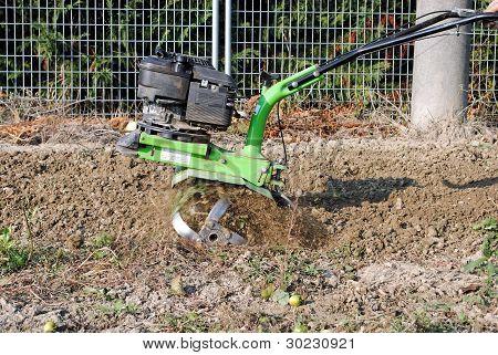 green rotary tiller working in the garden