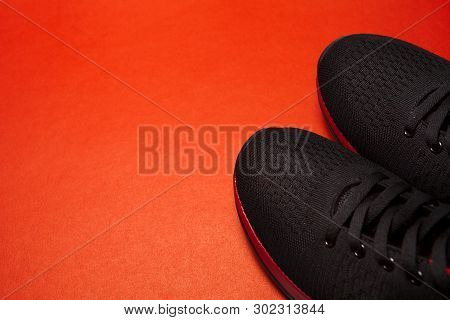 Sport Black Sneakers Isolated On Red Background