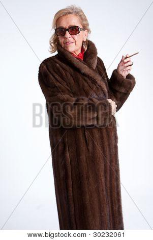 Smoking Senior lady wearing  a mink coat and sunglasses