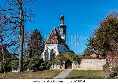 Little Church With A White Wall And A Brown Door
