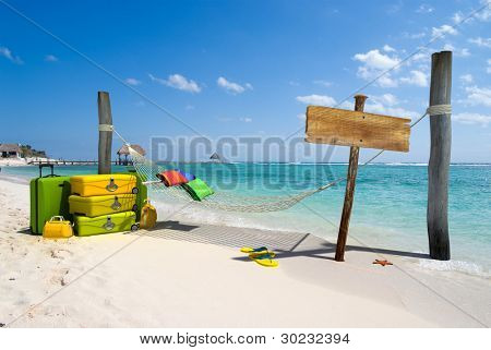 A hanging hammock, a wooden sign post , a pile of luggage, thongs and starfish on a beach resort