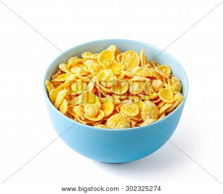 Dry Breakfast Cornflakes. Blue Plate Full Of Cereal. Isolated On White Background
