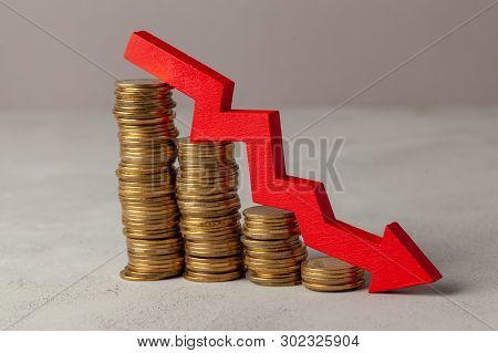 Green Arrow Down Over Stack Of Coins By Ladder On Gray Background