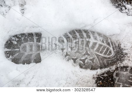 Foot Print Of A Human Shoe On The White Snow