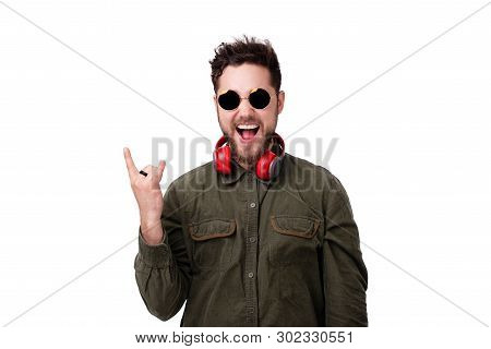Handsome Ypung Bearded Guy With Headphones And Sunglasses, Screaming And Doing Rock Gesture