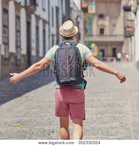 European Man In A Sun Hat Is Travelling Along The Narrow Street Of A European Town. His Arms Are Ope