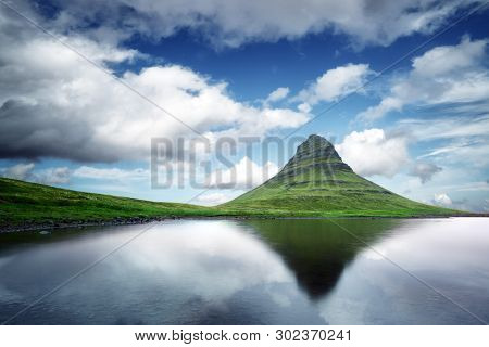Picturesque landscape with Kirkjufell mountain, clear lake and cloudscape in blue sky