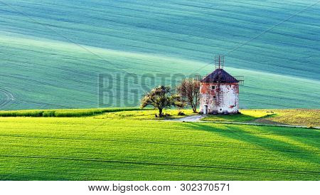 Gorgeous rural landscape with old windmill and green sunny spring hills. South Moravia region, Czech Republic