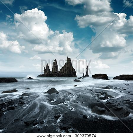 Picturesque landscape with basalt rock formations Troll Toes on Black beach, stormy ocean waves and cloudscape. Reynisdrangar, Vik, Iceland