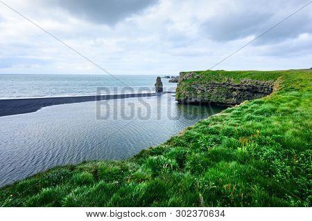 Picturesque landscape with green coast of Atlantic ocean in Iceland. Black beach, Reynisdrangar, Vik