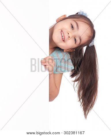Beautiful little girl child behind white blank board with empty space for text or picture. Smiling kid peeks out from behind white banner, isolated on white background.