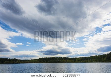 Beautiful Cloudy Sky Over A Small Lake With A Wooded Shore.