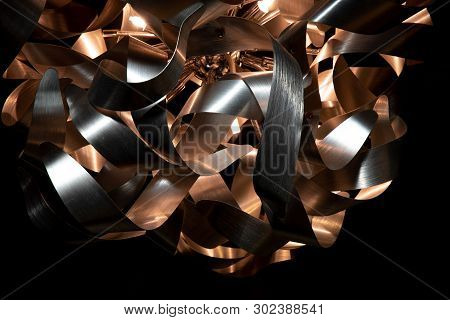 Silver And Copper Metal Curved Metal Ribbon Chandelier Closeup. Modern Metal Lampshade. Metallic And
