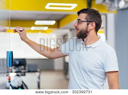 Serious Bearded Man In Glasses Is Drawing Business Strategy On The White Board With Marker. Computer